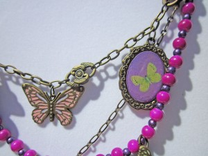 pink butterfly charm, yellow butterfly charm, violet beads