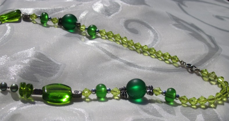 Necklace back closeup: peridot glass bicone beads, emerald green round glass beads, silver tone butterfly beads